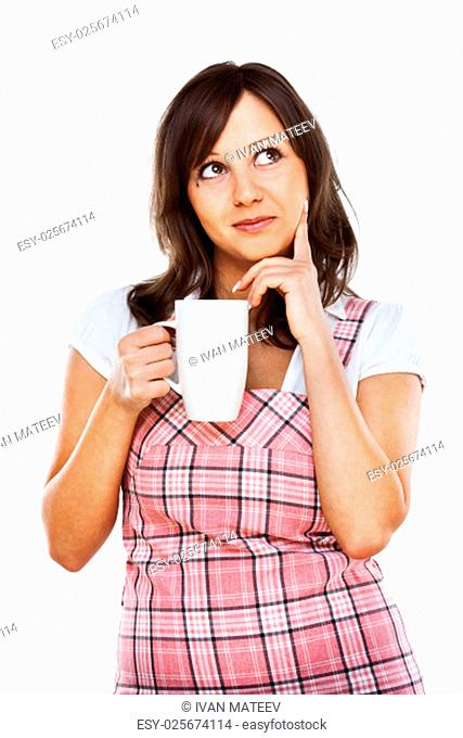 Young woman posing at camera over white background, close up - thinking of something with a cup of coffee and looking away