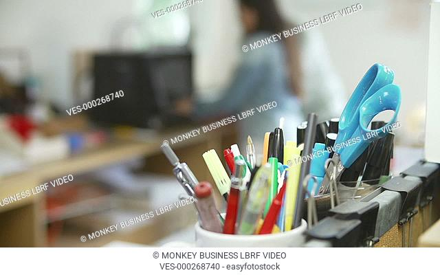 Focus is pulled from pencil pot in foreground to two architects working in office creating models for project using 3D printer