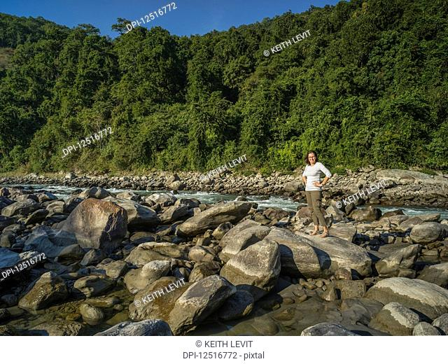 A woman stands on a large rock along the shoreline of a river with a lush forest in the background; West Bengal, India