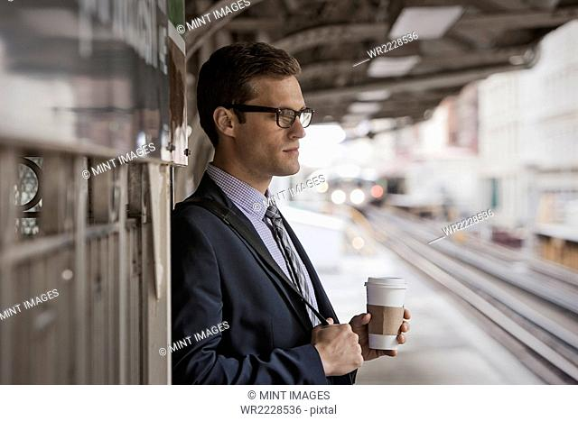 A working day. Businessman in a work suit and tie holding a cup of coffee on a railway platform