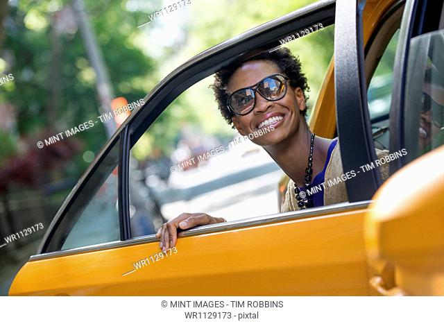 City life. People on the move. A woman getting out of the rear passenger seat of a yellow cab