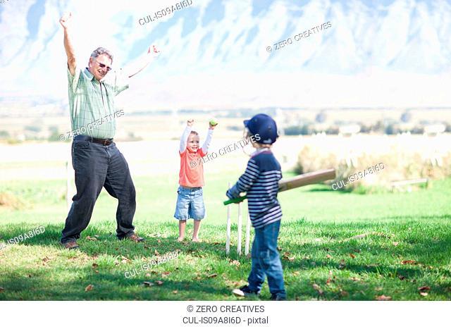 Boys grandfather playing cricket