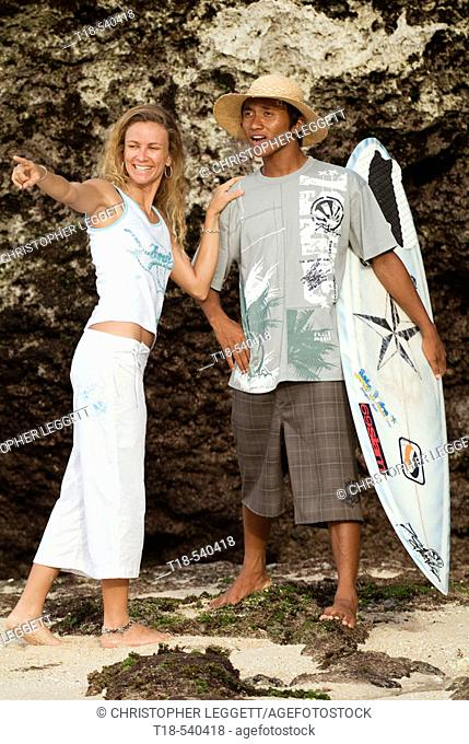 man holding surfboard with girl pointing to sea