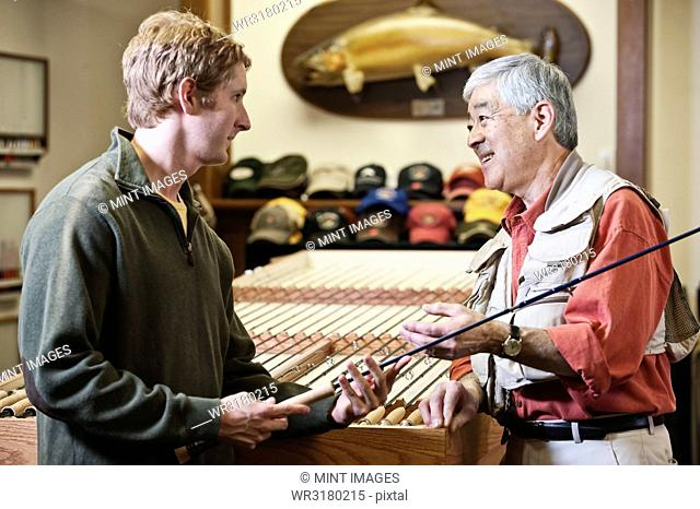 Asian American senior male owner of a retail fly-fishing shop talking to a young Caucasian male about the merits of new 5 weight fly fishing rod