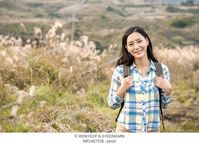 Portrait of young smiling female backpacker against silver grass field
