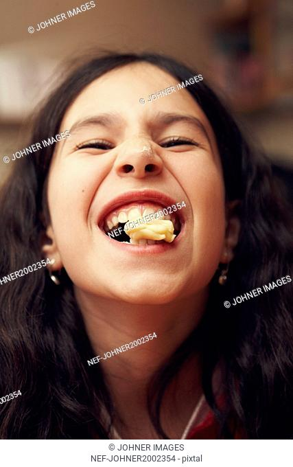 Portrait of smiling girl with cookie in her mouth