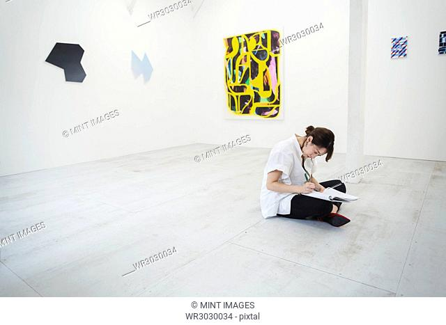 Woman with black hair wearing white shirt sitting on floor in art gallery with pen and paper