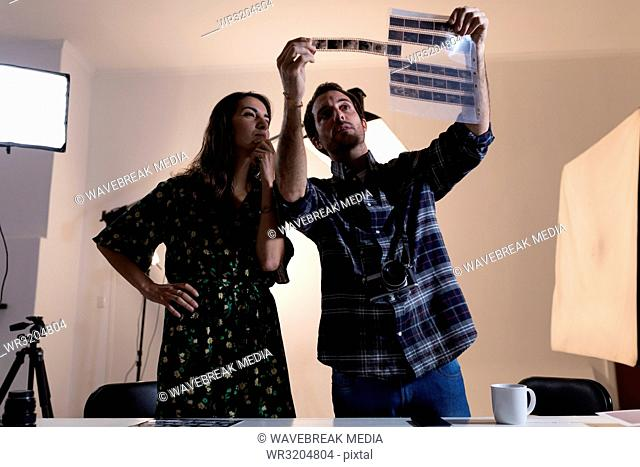 Male photographer and female model looking at negative filmstrip