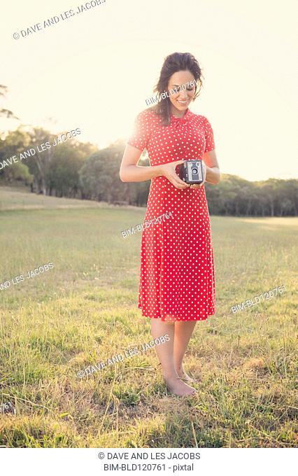 Hispanic woman using vintage camera