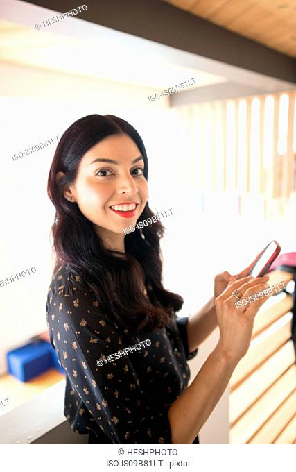 Portrait of young businesswoman on balcony with smartphone