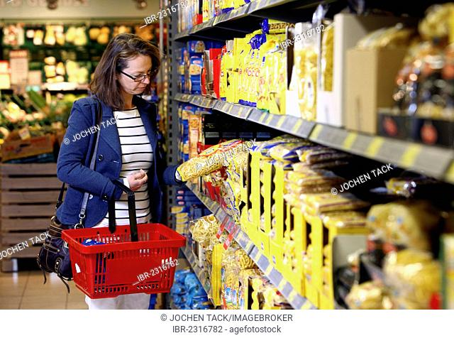 Woman purchasing noodles or pasta in a self-service grocery department, supermarket, Germany, Europe