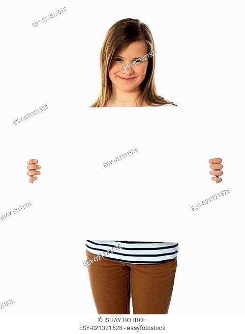 Smiling teenager showing blank white billboard