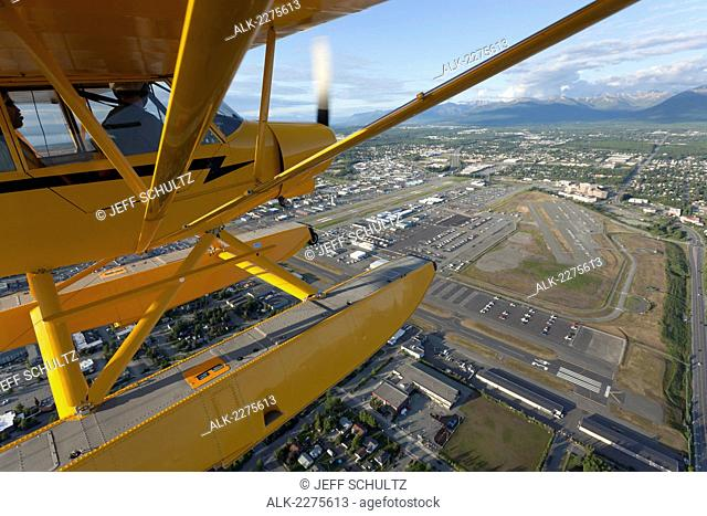 A Super Cub airplane flies over the city of Anchorage, Alaska with the Merrill Field Airport below, Summer, Southcentral, Alaska