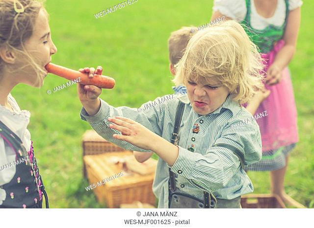 Germany, Saxony, girl biting off a carrot