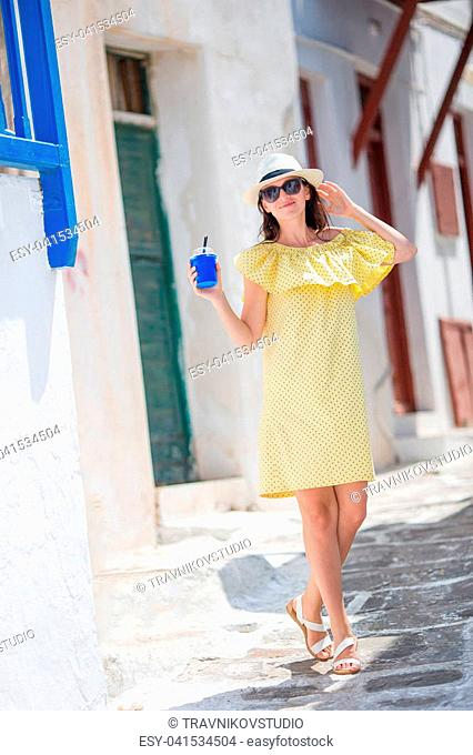 Young woman walking in narrow streets of old greek village