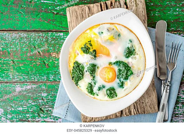 Florentine eggs with pureed spinach on the wooden table top view