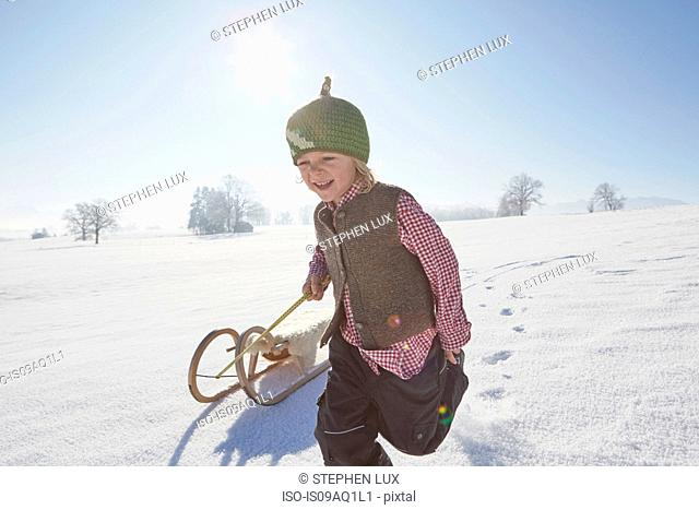 Young boy running, pulling sled