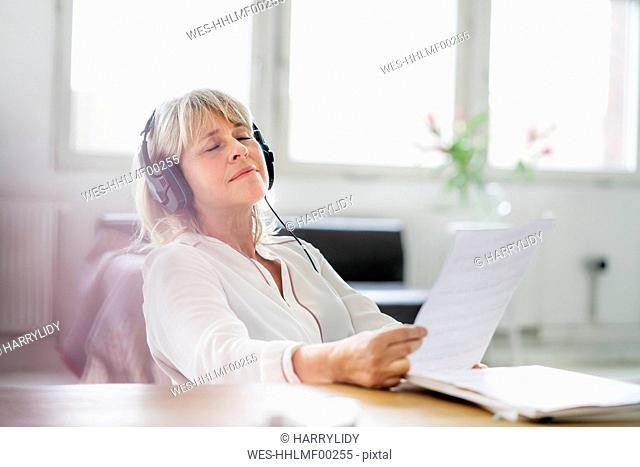Relaxed mature businesswoman wearing headphones at desk