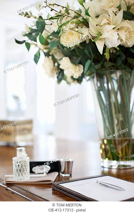 Rose bouquet and notepad on luxury desk