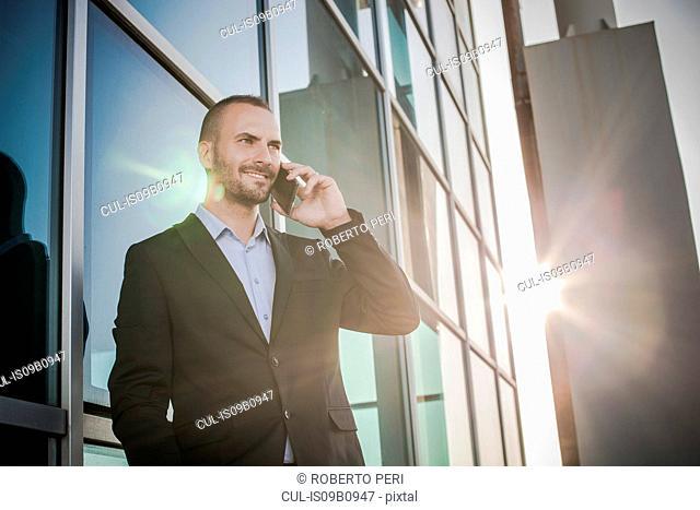 Businessman outside office chatting on smartphone, Cagliari, Sardinia, Italy
