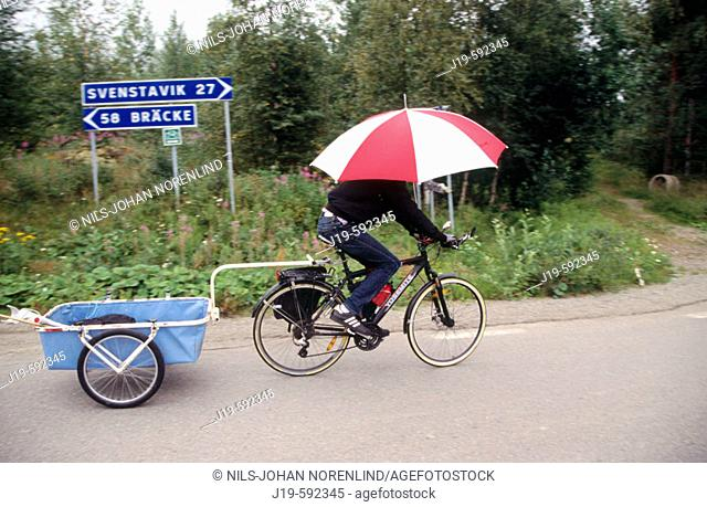 Bicycle tourist with a cart and 'umbrella in rain'. Jamtland. Sweden