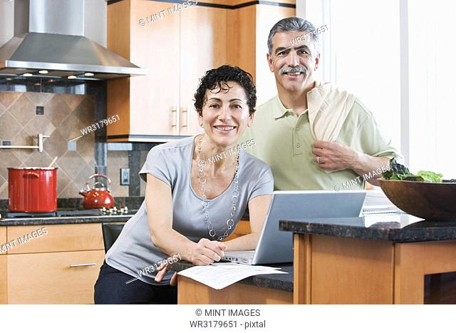 Caucasian man and woman in a kitchen using a laptop