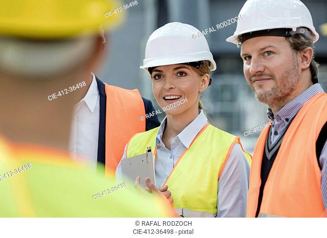 Smiling engineers meeting at construction site
