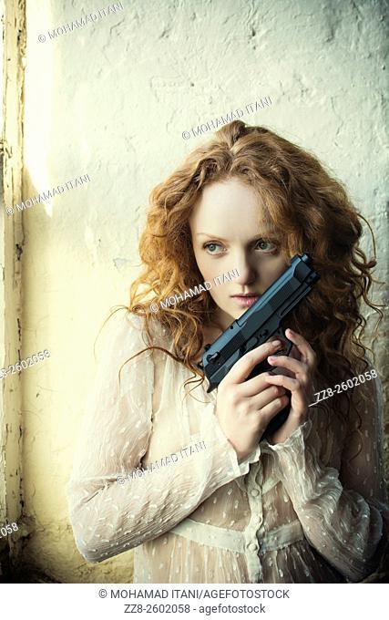 Redhead woman holding a gun