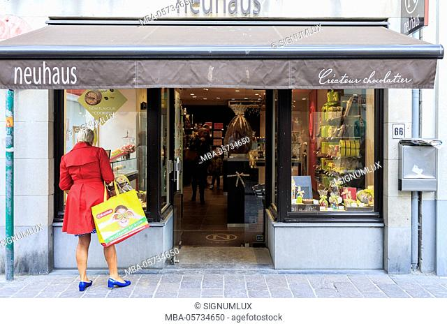 Belgium, West Flanders, Bruges, a funny-dressed woman is watching at a shop window