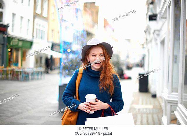Young woman walking in street, holding coffee cup and shopping bag