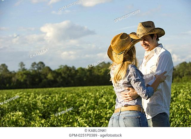 young couple dancing in field wearing cowboy hat