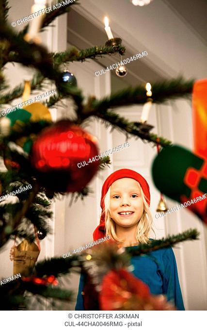 Smiling girl admiring Christmas tree