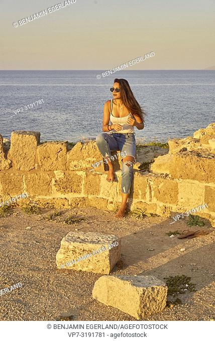 woman at seaside sitting on ancient ruins. In Chersonissos, Crete, Greece