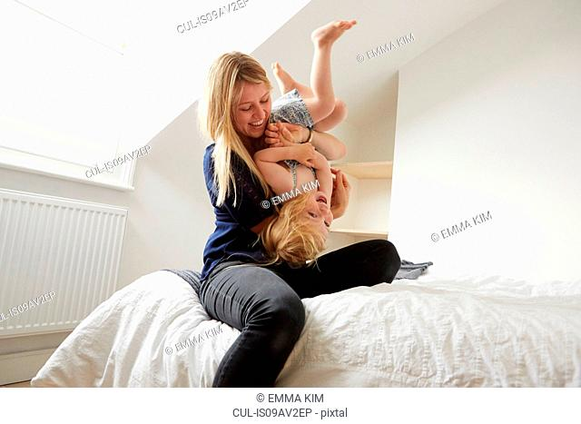 Mid adult woman turning toddler daughter upside down on bed