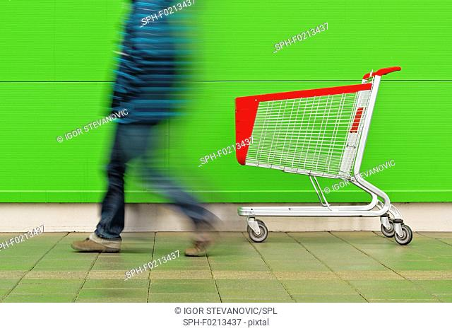 Man walking by empty shopping trolley