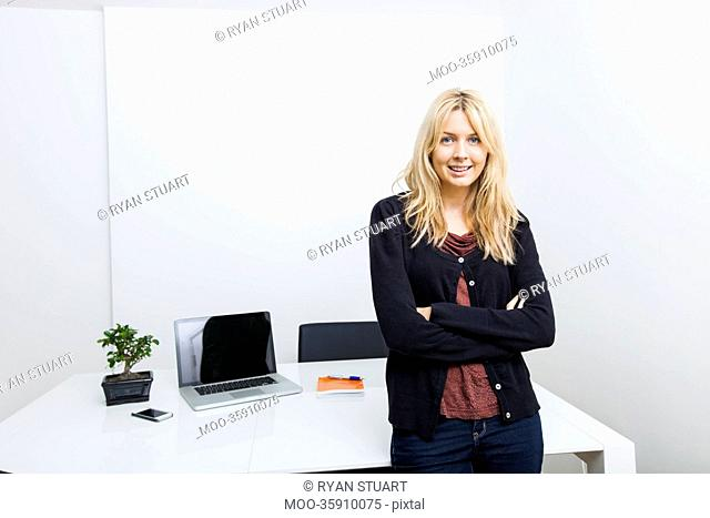 Portrait of happy businesswoman standing arms crossed in office