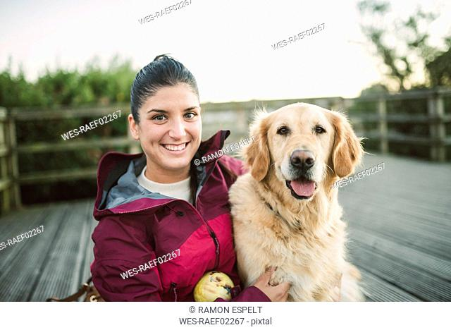 Portrait of a happy young woman with her Golden retriever dog outdoors