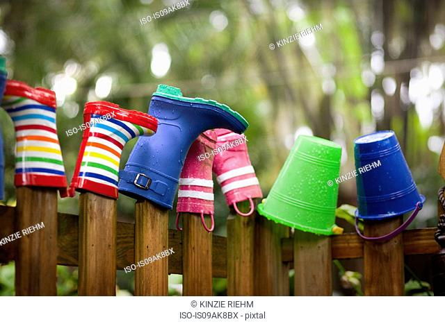 Row of rubber boots and buckets on top of garden fence