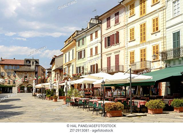 picturesque buildings and outdoor cafes on Motta square at historical touristic village, shot on bright summer day at Orta San Giulio, Novara, Cusio, Italy