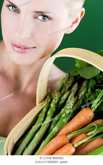A young woman holding a basket full of vegetables, close-up