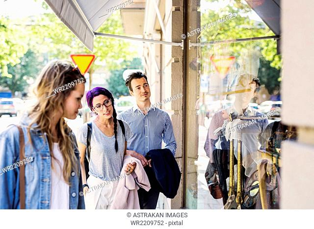 Male and female friends window shopping in city