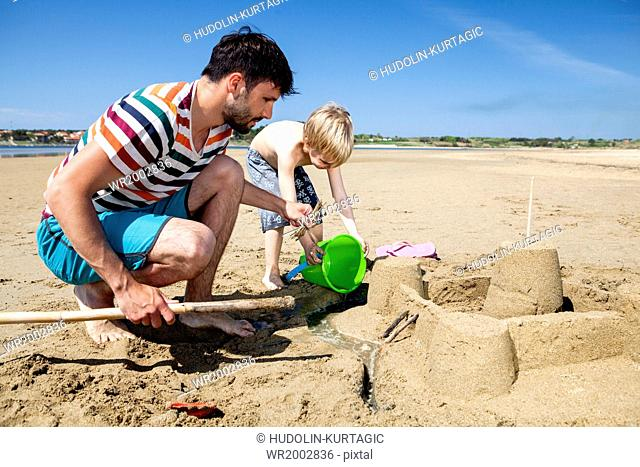 Father and son on beach making sandcastle