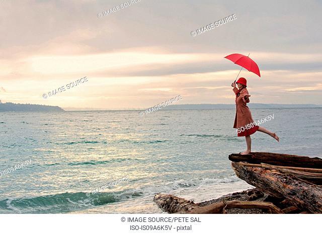 Woman with umbrella on coastal cliff