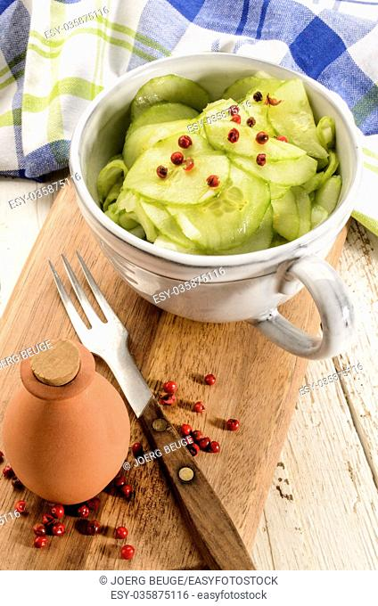 cucumber salad in a grey cup, made with vinegar, onion, olive oil and red peppercorn on wooden board