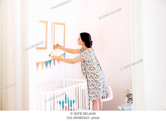 Pregnant mid adult woman measuring picture frames in childs nursery