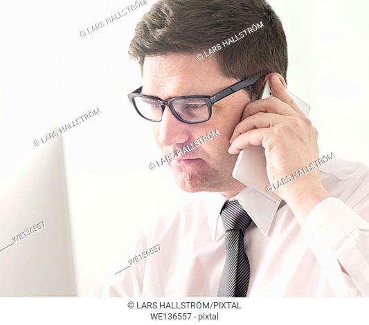 Businessman talking on cell phone and working with computer in office