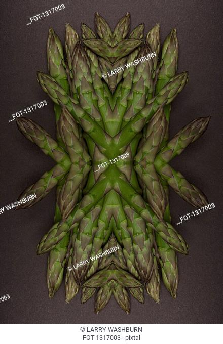 A digital composite of mirrored images of an arrangement of asparagus