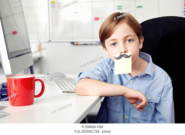 Boy with adhesive note covering mouth, drawing of moustache