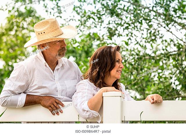 Mature couple leaning against ranch fence looking away, Bridger, Montana, USA