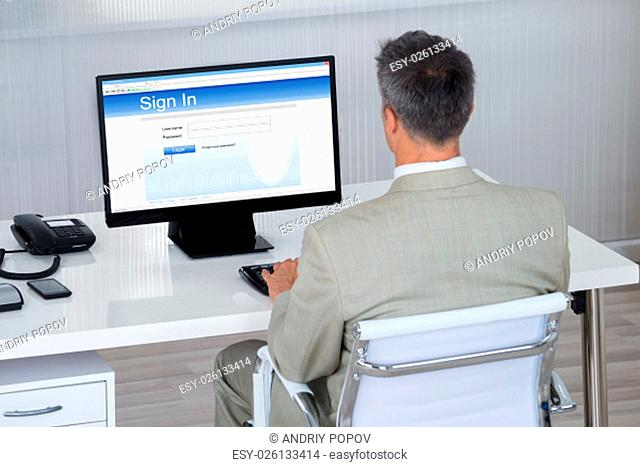 Rear view of businessman signing into website at desk in office